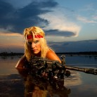 Blonde warrior woman in a lake at sunset, armed with a large rifle