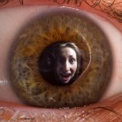 Portrait of woman's face reflected in her own eye