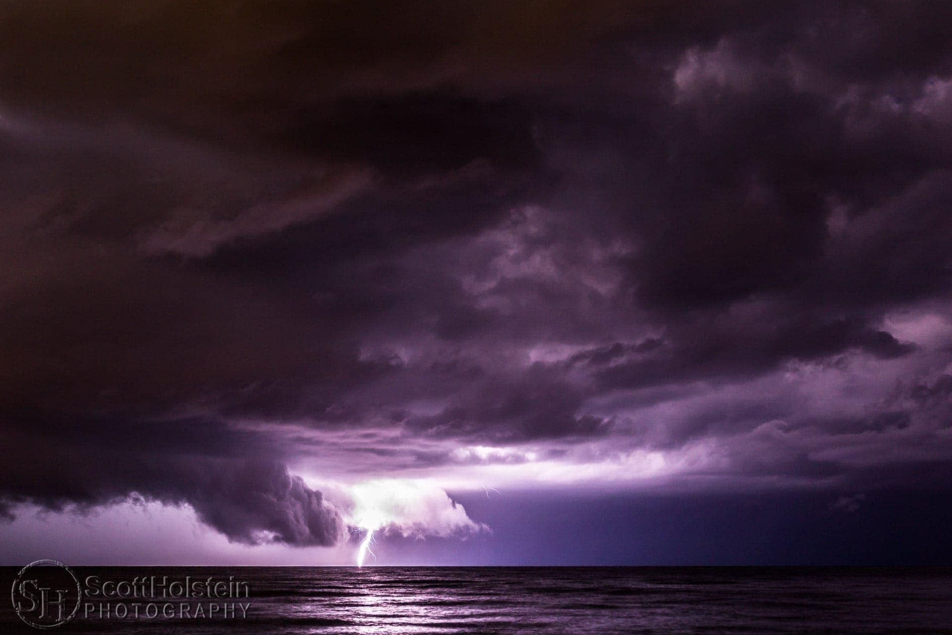 Beach Lightning: A dramatic summer thunderstorm at night flashes lightning over water off the beach in Venice, Florida.