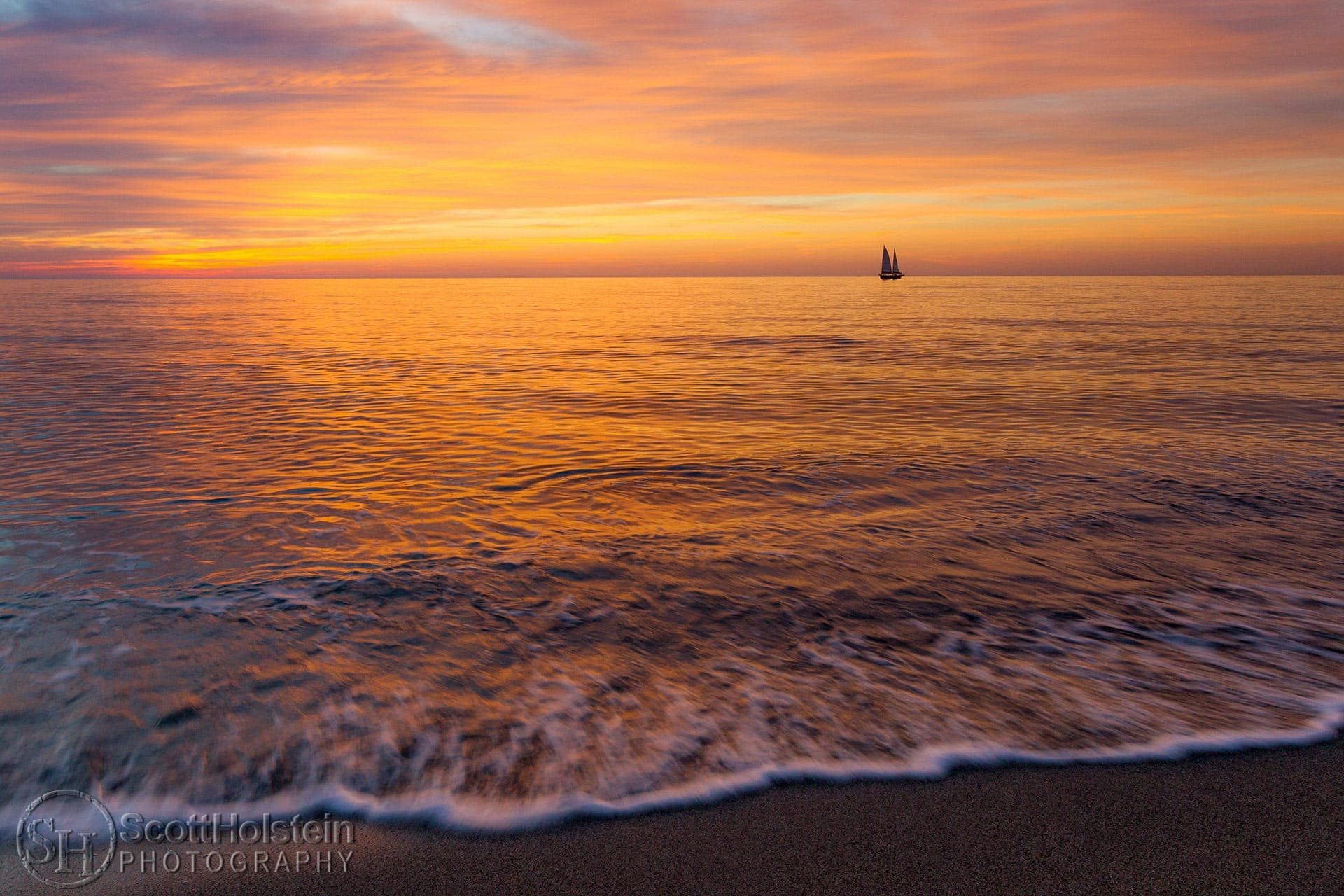 A sailboat sails on the horizon during a pastel sunset off of the beach in Venice, Florida.