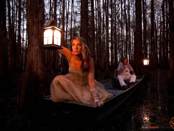 A beautiful woman holding a lantern peers out into a swamp at dusk.