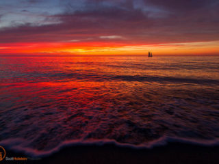 Florida landscape photography of a sailboat off the beach during a vibrant sunset in Venice.