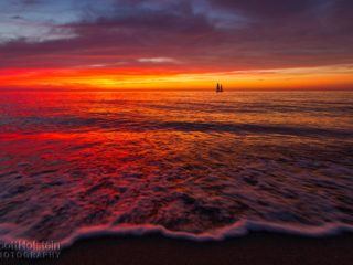 A sailboat sits on the horizon during a vibrant beach sunset in Venice, Florida.