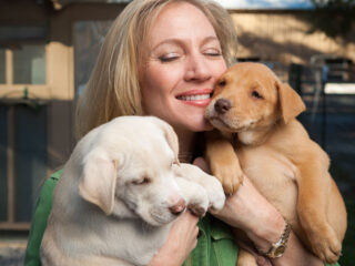 Laurie Hood of Alaqua Animal Refuge cuddles with two puppies.