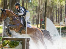 Water splashes as a horse and rider jump over a fence in a water feature during the Red Hills International Horse Trials.
