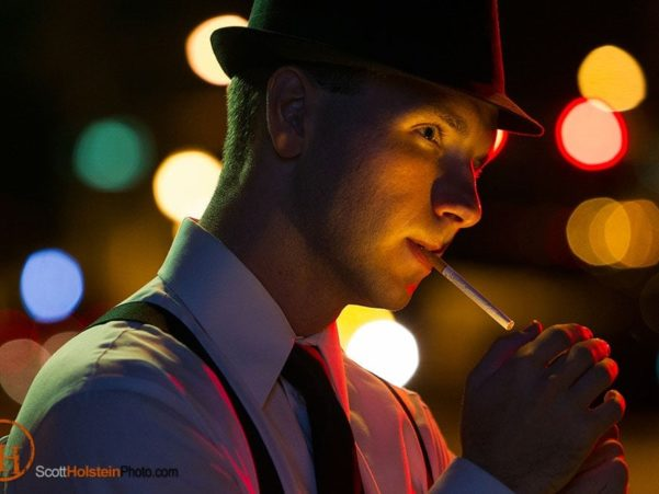 A detective in a fedora lights a cigarette at night in front of glowing street lights in a dramatic portrait.