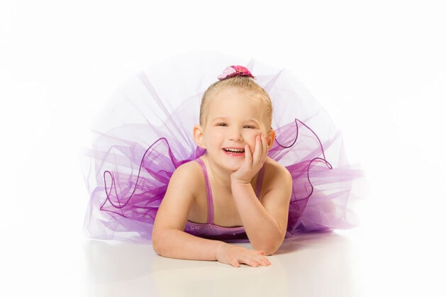 Portrait photography of a young ballerina in a tutu laying down and laughing.