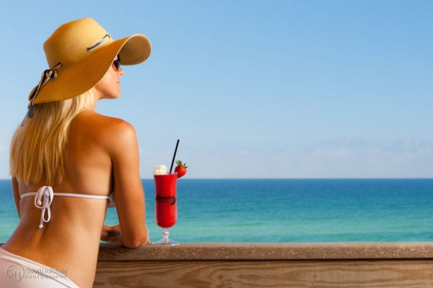 Hospitality photography sample: Florida beach resort, featuring a woman in a floppy hat with a drink overlooking the gulf near Destin, Florida.