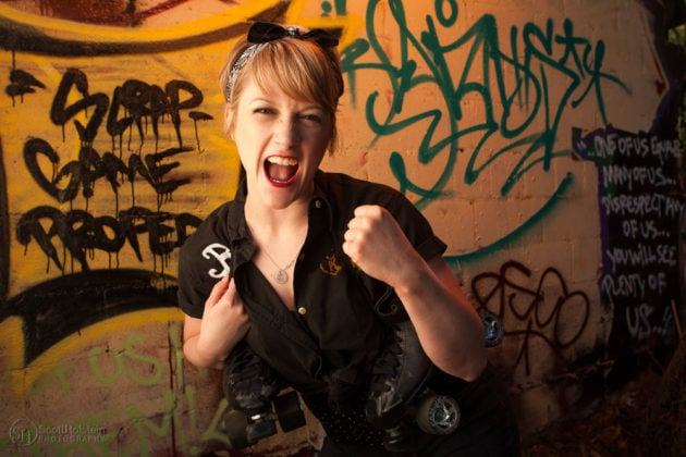 Environmental portrait photography sample featuring a roller derby girl passionately yelling on location in front of a graffiti wall.
