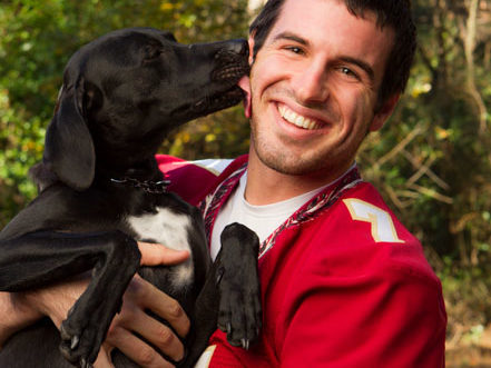 Portrait of NFL quarterback Christian Ponder's dog licking his face by Tallahassee photographer Scott Holstein.