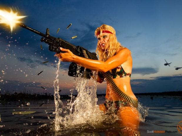 Creative photography of a warrior woman emerging from the water while firing a machine gun.