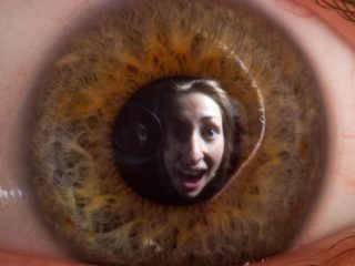 Creative photography of a woman's face reflected in the pupil of her own eye.