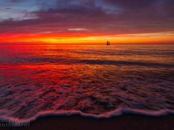 A sailboat sails during a vibrant sunset just off the beach in Venice, Florida.