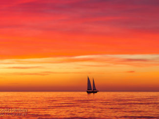 A sailboat in the Gulf of Mexico is silhouetted against a vibrant, pink and orange sunset in Venice, Florida.