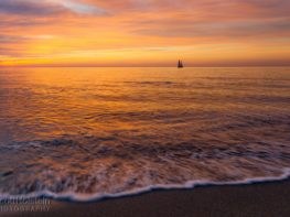 A sailboat punctuates a pastel-colored sunset in the Gulf of Mexico off of a Florida beach.