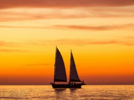 A sailboat is silhouetted in front of the afterglow of a yellow and orange sunset in the Gulf of Mexico in Venice, Florida.