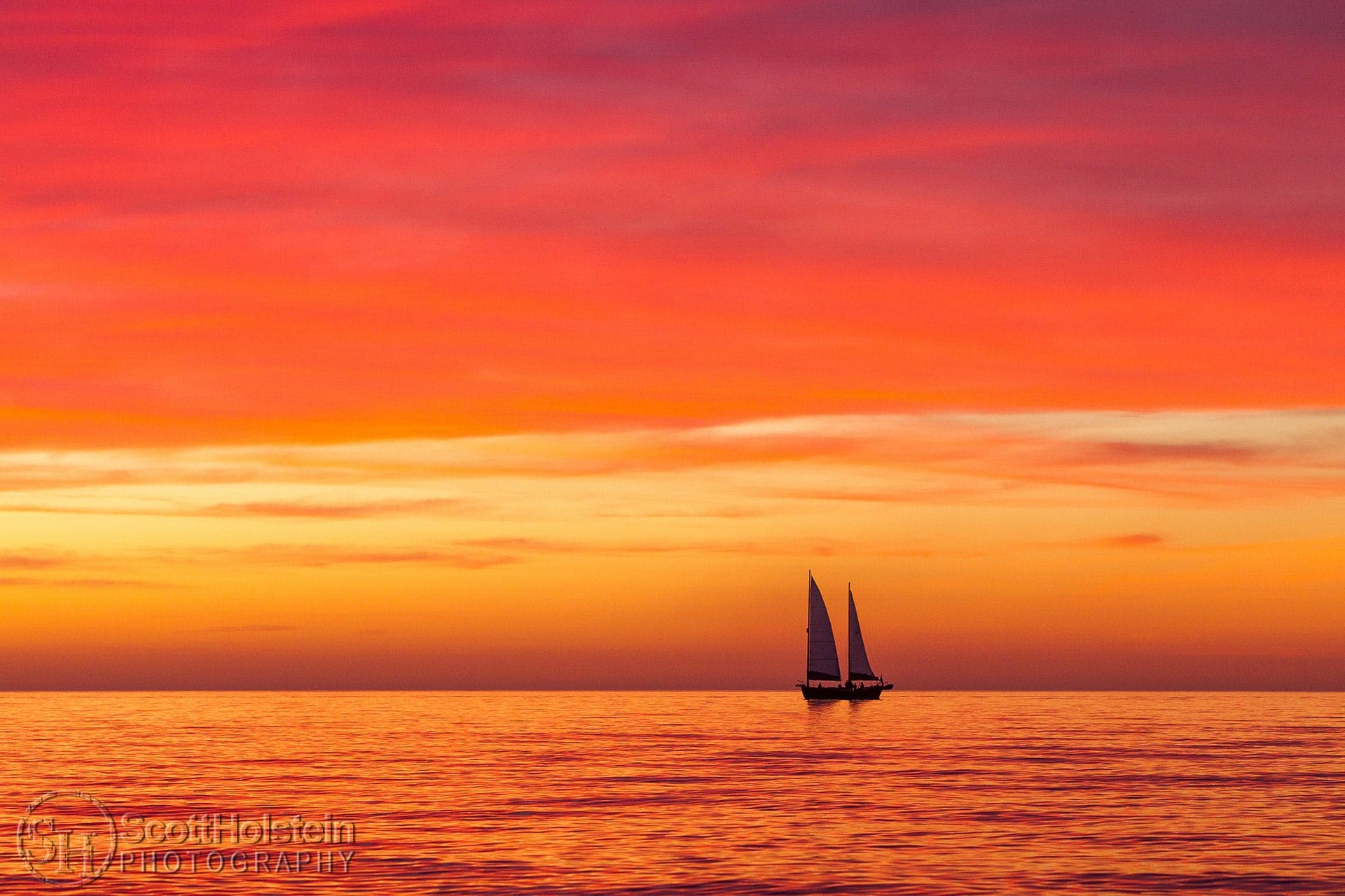 A sailboat is silhouetted against a pink sky during a Florida beach sunset.