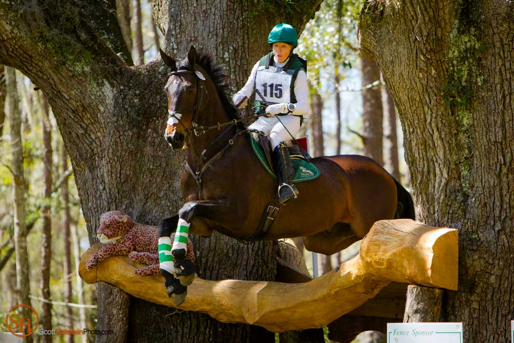 Rider and horse jumping between oak trees on a cross country course.