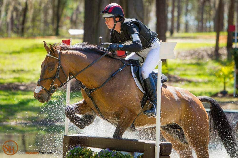 A horse trips over a water jump during a Cross Country course.