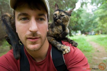 Editorial photographer Scott Holstein with a cat hitchhiker riding on his shoulders at Caboodle Ranch.