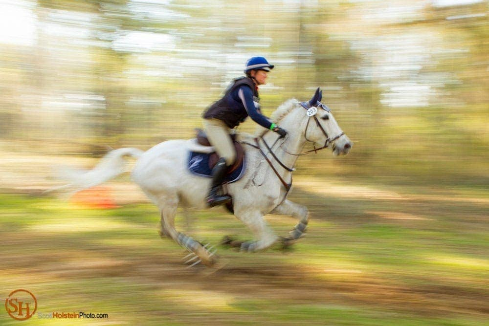 A horse and rider gallop in a blur on the Cross Country Course at Red Hills Horse Trials