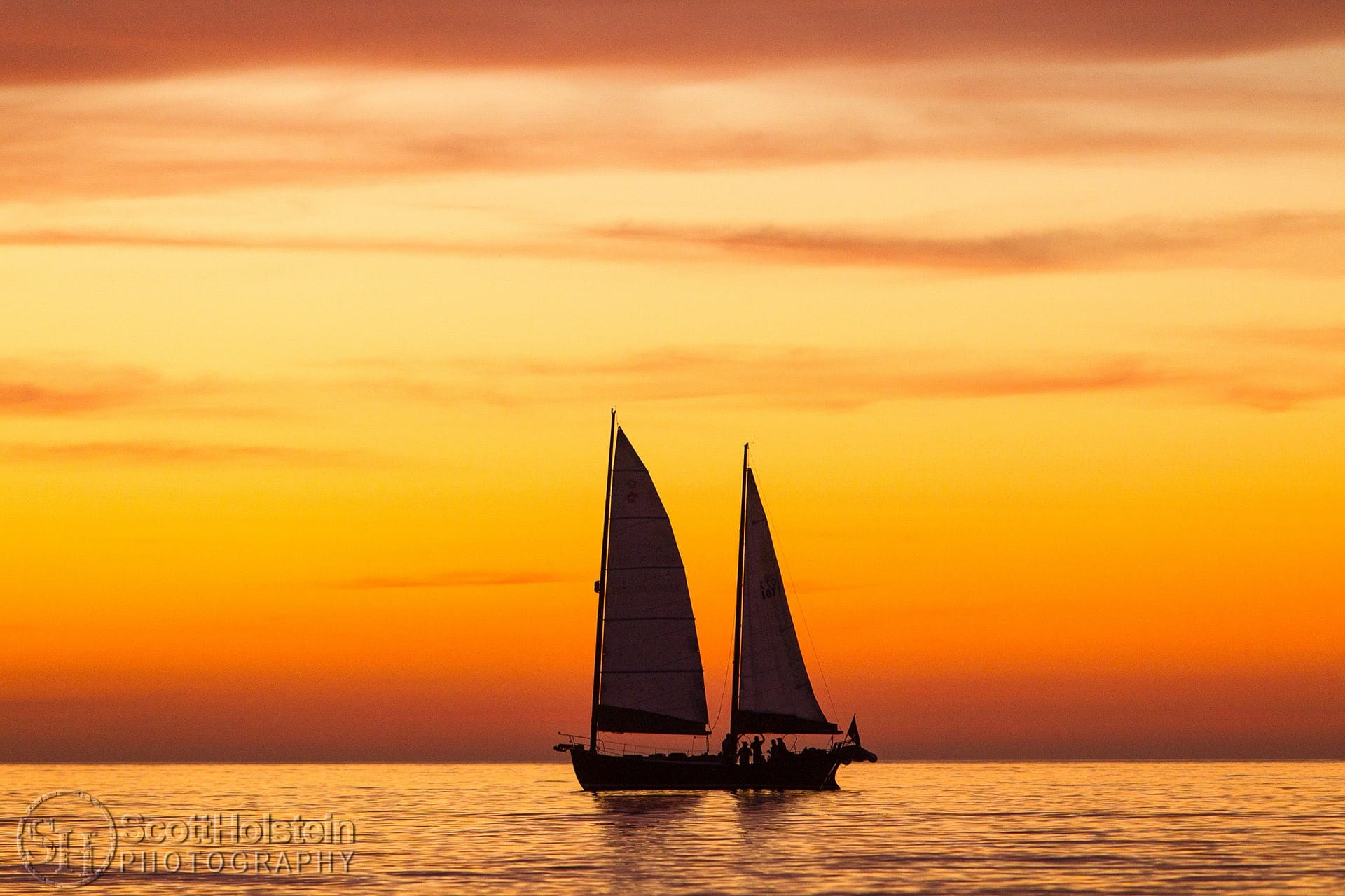 Silhouette of a sailboat during an orange sunset in Venice, Florida.
