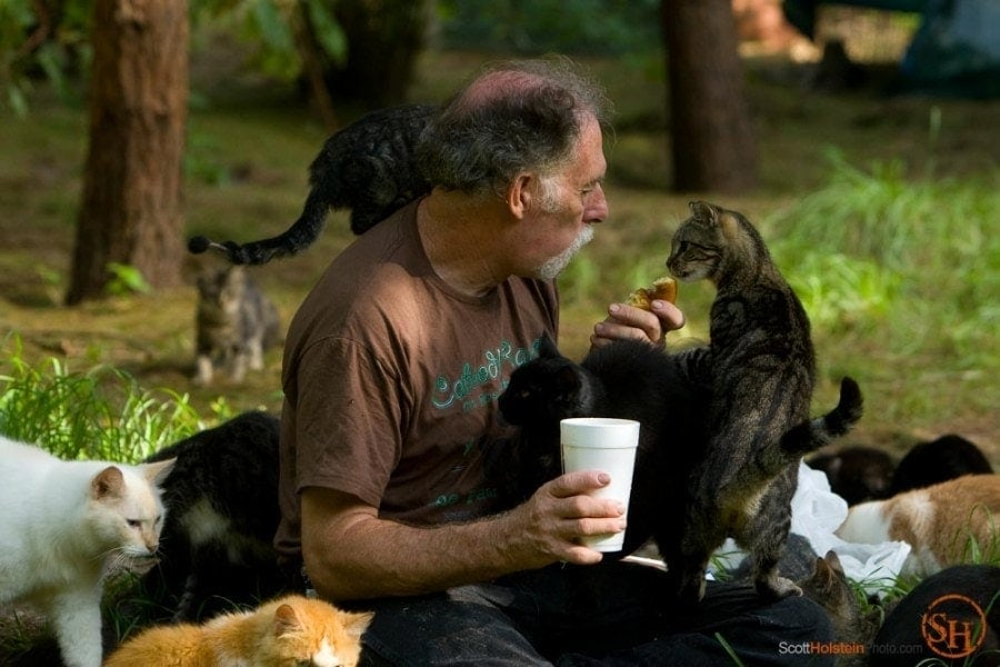 Photo of Craig Grant sharing his doughnut with a cat by Tallahassee magazine photographer Scott Holstein.