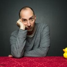 Portrait photography of actor Tony Hale looking bored while sitting with a yellow toy duck in Tallahassee, Florida.