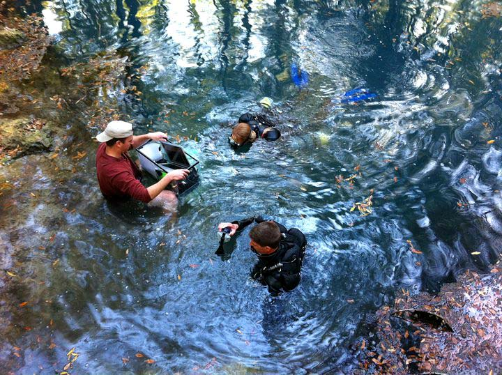 Behind-the-scenes photo of Tallahassee photographer Scott Holstein photographing cave divers in a the water.