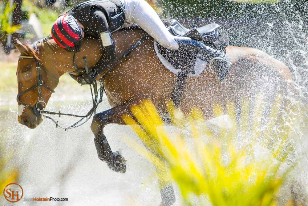 A rider is thrown from the saddle and clings to the horse's neck after the horse stumbled on a water jump.