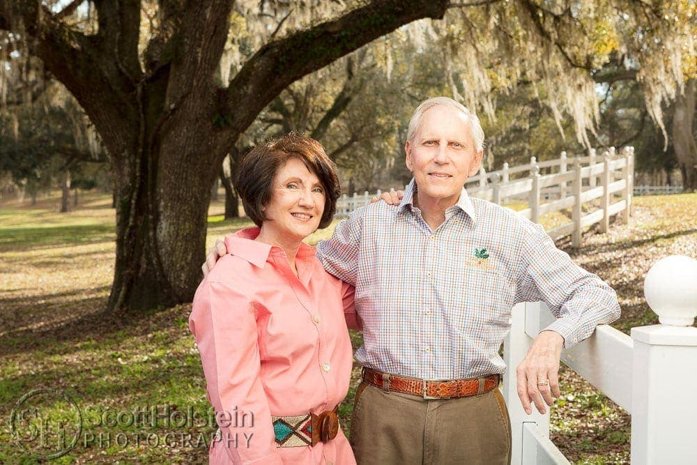 "Dr. Thomas Kent ""T.K."" and Virginia ""Ginger"" Wetherell pose alongside the fence in front of a Spanish moss-draped live oak tree on their farm in Lamont, Florida."