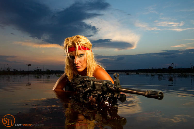 A warrior woman partially submerged in a lake with a machine gun.