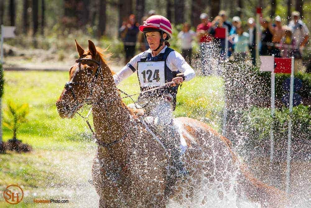 Water sprays up around a horse and rider at Red Hills Horse Trials.